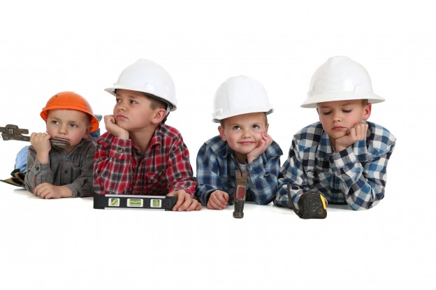 Boys laying down with tools wearing construction hardhats